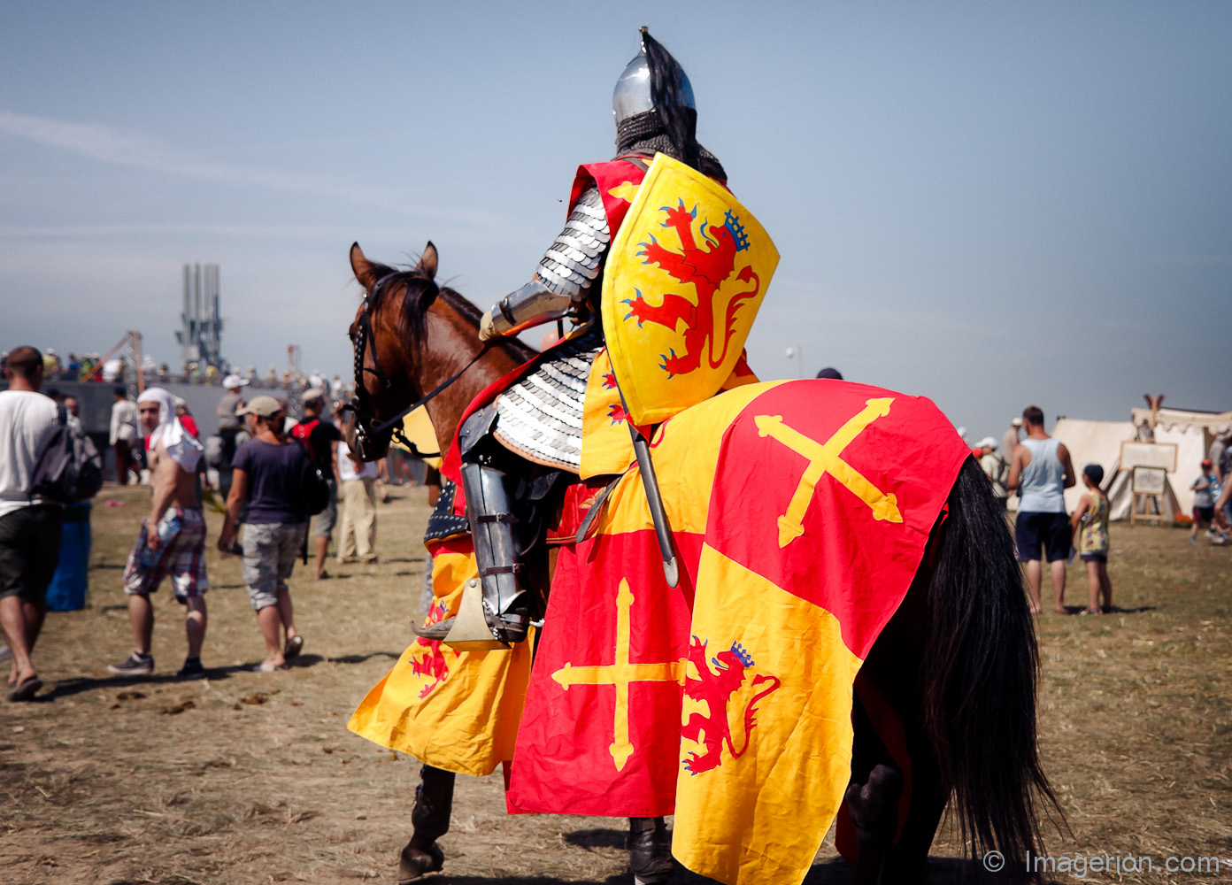 A knight on horseback, yellow and read coat of arms