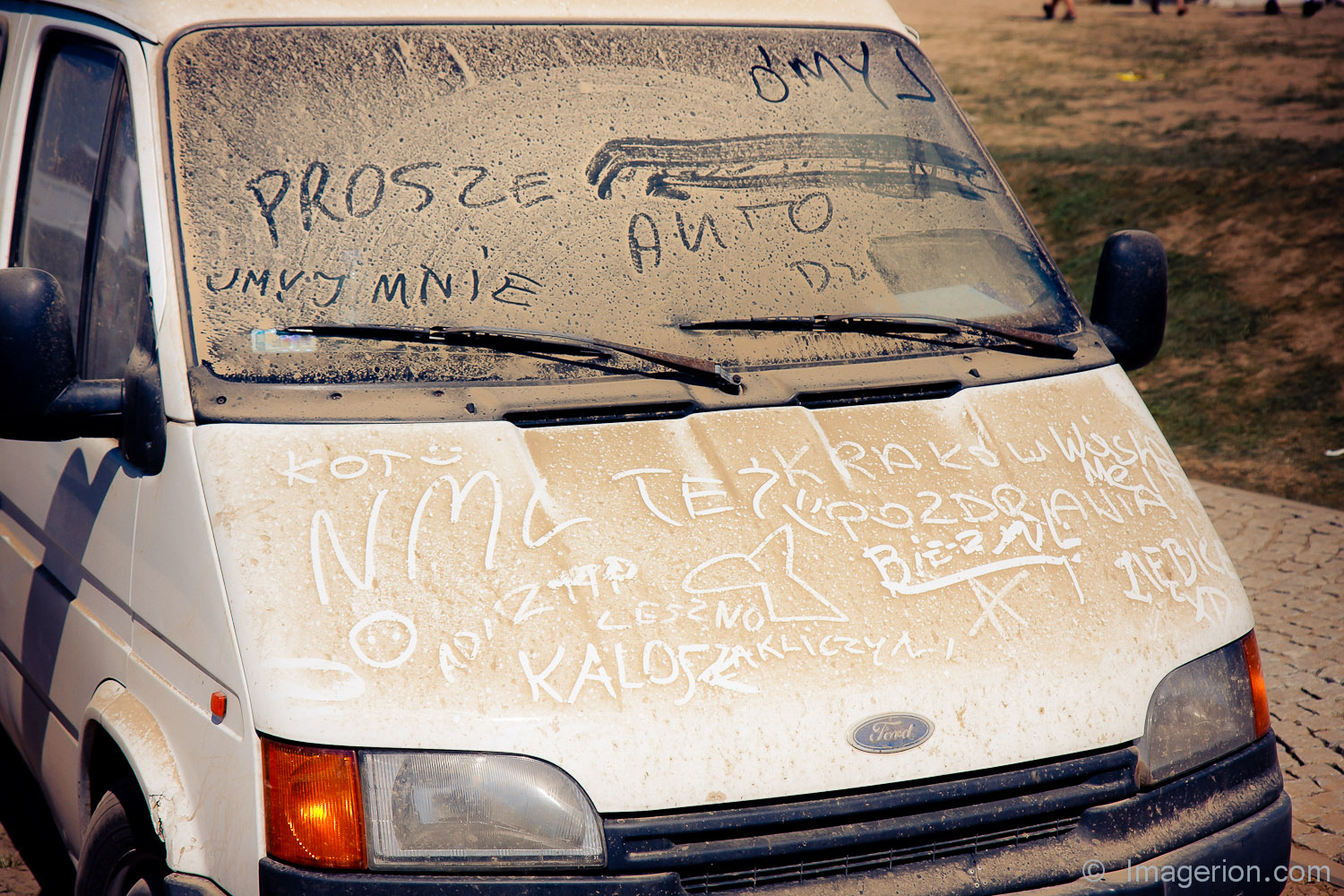 White car covered with the dust and inscriptions on it