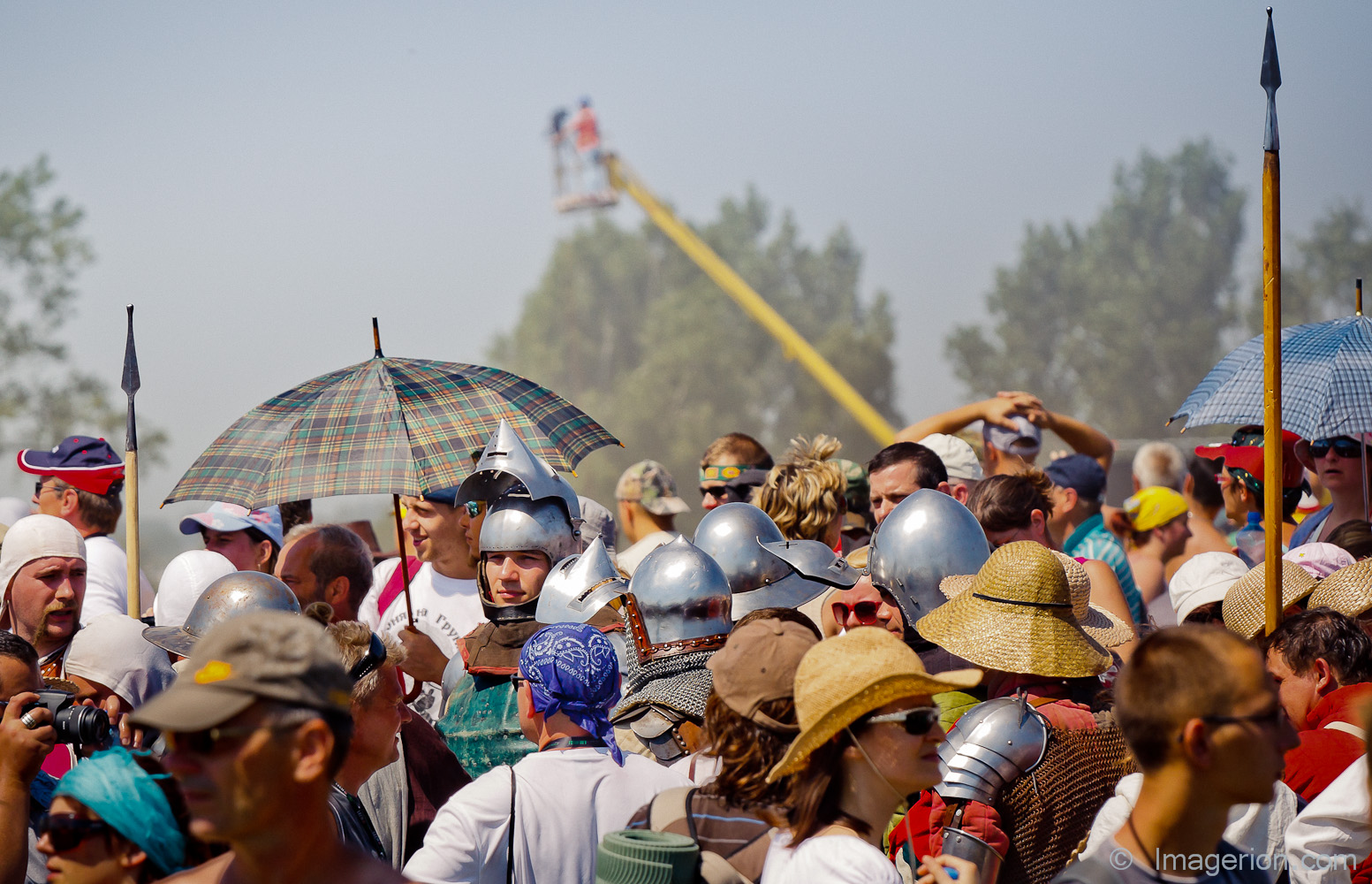 Armored medieval knights among modern crowd of people