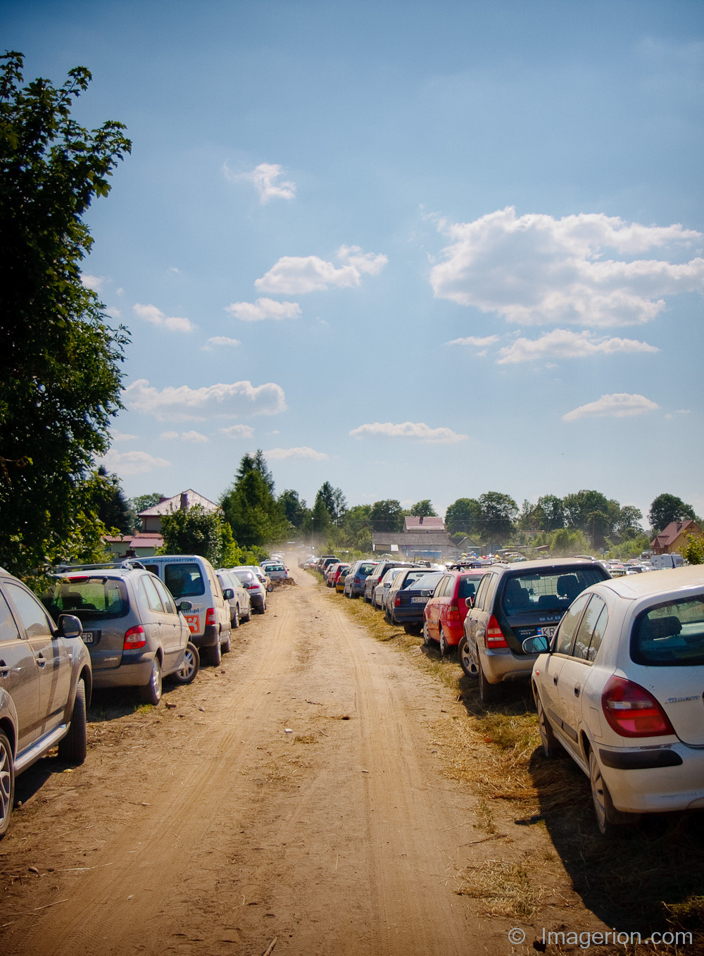 Two lines of cars parked by the dusty country road