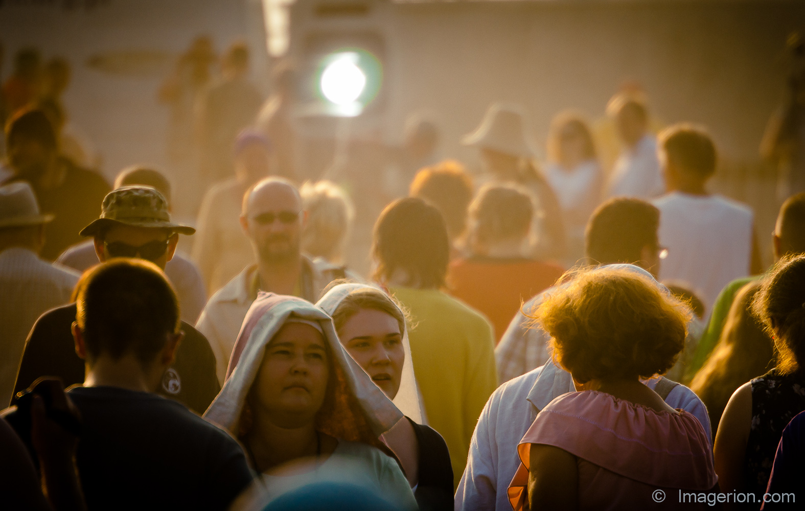 Modern crowd in a mist of dust and medieval women walking through
