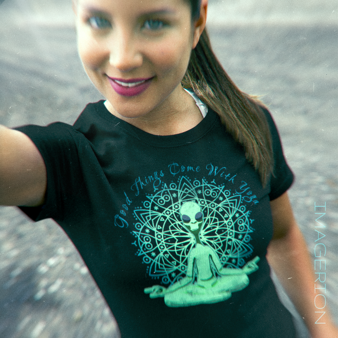 Woman wearing a tshirt with alien yoga design, yoga quote