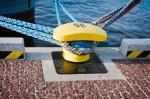 Image of bollard. Yellow bollard and mooring lines