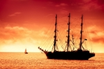 Image of journey. Tall ship sailing in red