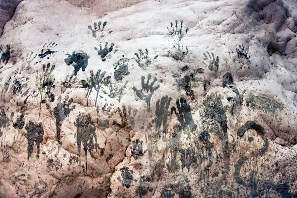 Handprints on a stone wall