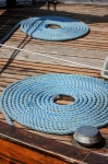 Image of sailing. Blue ropes rolled in order on the boat deck