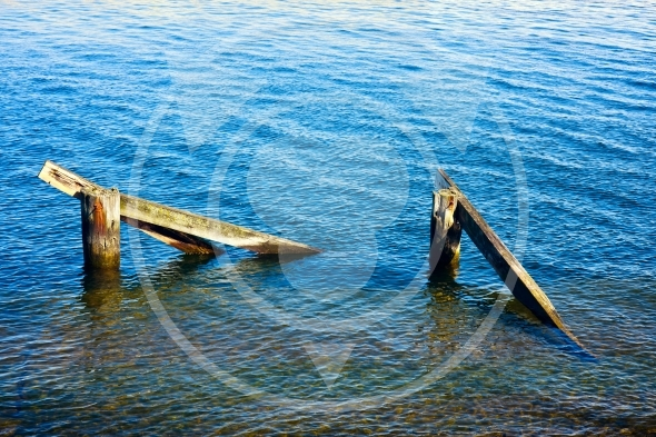 Wooden pier remnants in sea water