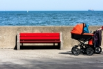 Image of bench. Baby strollers on a walk and empty bench