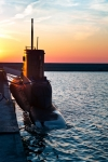 Image of warship. Submarine in port at sunset