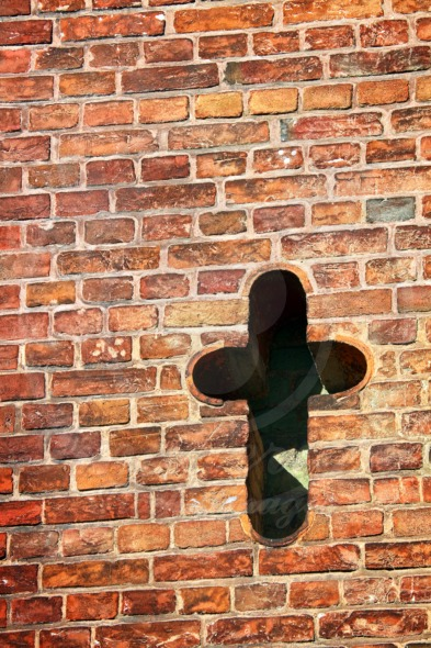 Cross in old brick wall