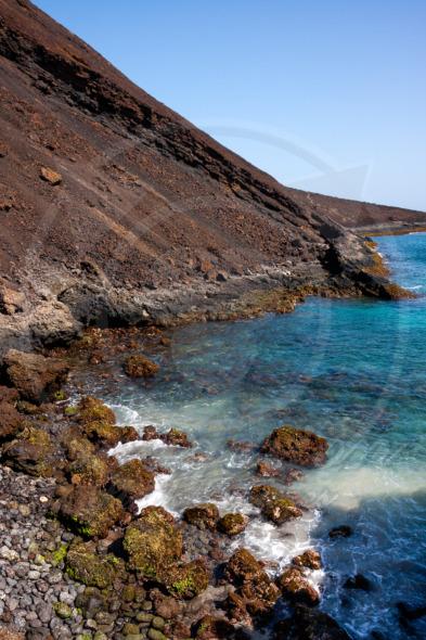 Extinct volcano crater, sharp boulders, basalt ocean shore line. Sao Vicente Island in Cape Verde