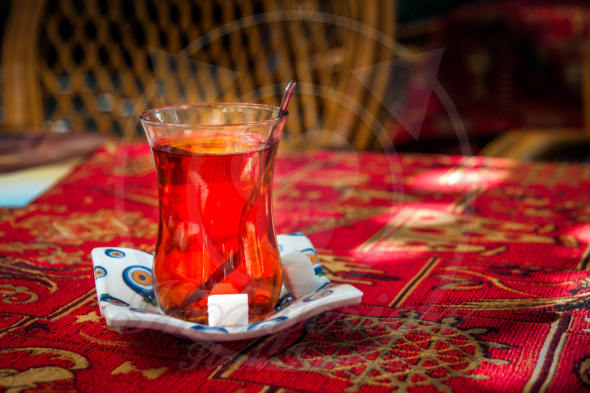 Turkish tea, sugar, spoon, on a saucer with an Evil Eye