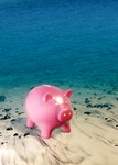 Image of vacation. Piggy bank at the sea shore, saving money concept