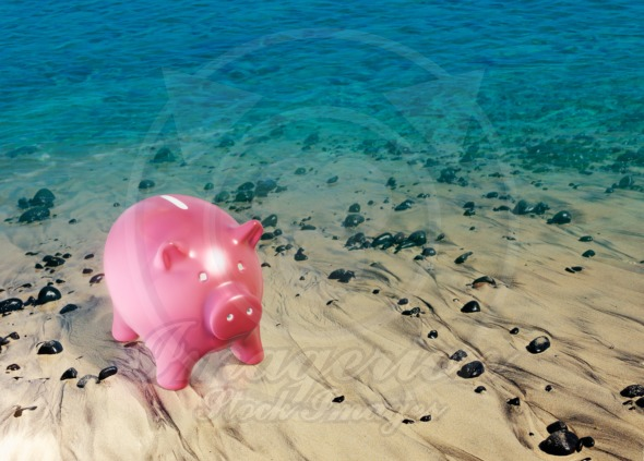 Pink piggy bank on the beach, saving money concept